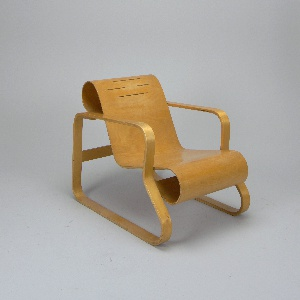 Curved bent birch plywood seat joined to frame composed of ribbon-like curved, laminated bent birch elements forming legs/arms; form reinforced by solid birch cross pieces at curled ends of back and seat, and at rear legs.