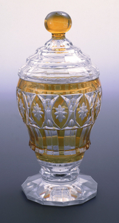 Ogee-shaped body on short stem with faceted knop and 12-sided flaring foot; sides cut to reveal clear glass behind flashed amber layer in pattern of rosettes in oval frames and underneath alternate colored vertical stripes; domed, stepped cover, faceted, with amber ball finial.