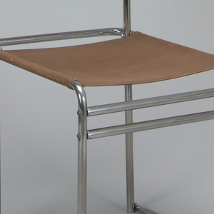 Upright, rectangular bent tubular steel frame; back and seat consisting of panels of brown Eisengarn canvas.