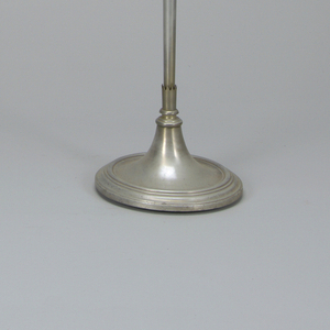 Electric floor lamp with circular base and telescoping stand whose joints are wrapped in jagged-cut cuffs; terminates at top with repeated jagged motif from which feather-like blown glass petals curl open, held in place by vertical metal pickets.