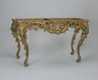 "Side table of carved and gilt wood, supporting contoured ""jaspe rubane"" marble top with molded edge. Four serpentine legs entwined by deeply carved leafy branches; feet scrolled under on small supports; curved frieze carved with leafy branches and central symmetrical acanthus leaf motif."