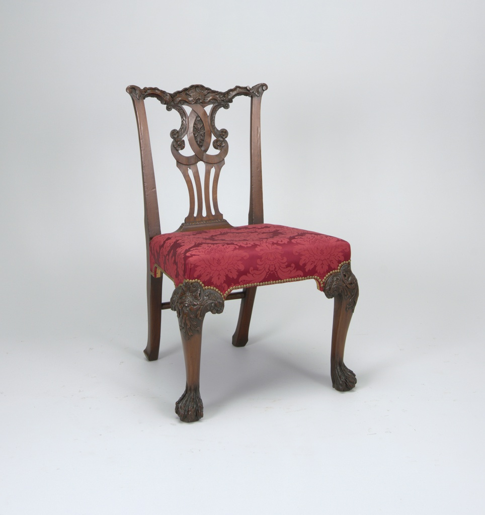 A four leg chair with a decorative cut out back and carved legs. The seat is upholstered in a red floral silk.