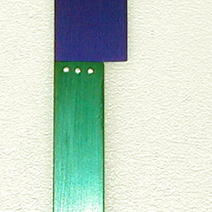 Flat rectangular aluminum handle with brushed surface, adonized green. Rectangular blade adonized purple with rounded outer point and bevelled cutting edge. Blade affixed to handle side with three silver rivets.