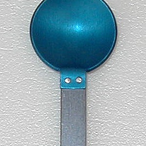 Flat rectangular handle of grey aluminum; brushed surface. Circular, concave bowl with flanged extension to overlap handle. Bowl affixed to handle with two silver rivets. Bowl anodized blue.