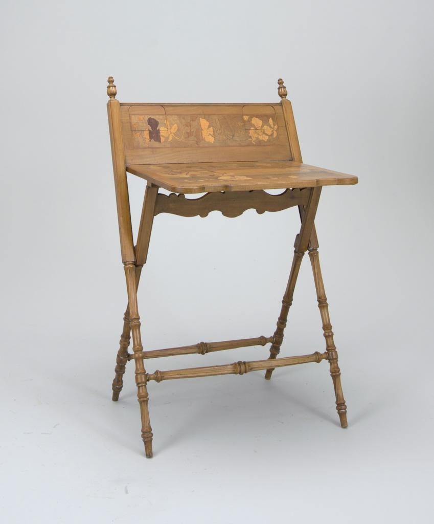 The folding top inlaid in contrasting colors of wood with floral and foliage decoration. Carved legs supporting a flat work surface and a backboard, both decorated with inlaid soft-wood marquetry of flowers, the backboard including two small fold-down shelves to support inkwell, pens, etc.