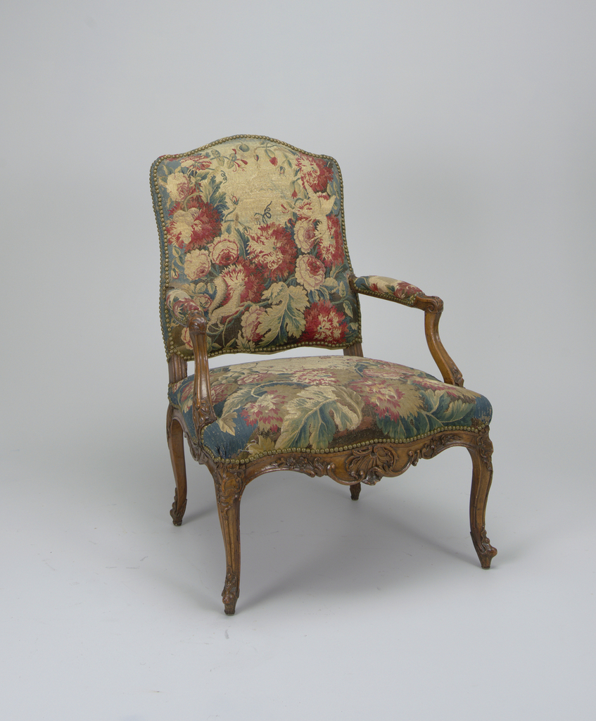 This set of chairs (2) consists of two antique Aubusson tapestry covered armchairs of the Louis XV period.  The armchairs' curved backs and seats are upholstered in reddish-blue floral fabric.  The wooden armrails are upholstered on their upper side.  The fabric is attached via metallic buttons.  The frontal part of the seat bottom is decorated in a wood, in a carved floral motif.