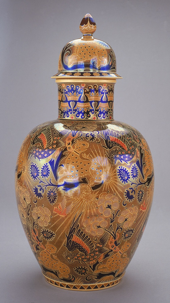A matching vase and cover depicting an outdoor scene with birds and other animals in brown tones with accents in blue and red. The vase has a long neck and the lid is dome like with round knob on top.