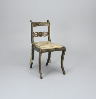 Two side chairs,  adaptation of Klismos form, lacquered black, with gilding.   Back uprights form continuous curving line both with seat and front legs and with lyre on each side of center.  Medallion containing woman's (Medusa?) head.  Each chair with modern boxed seat cushion, grey background, yellow stripes and multi-colored flowers, tied to rear uprights with tassled gray silk cord.