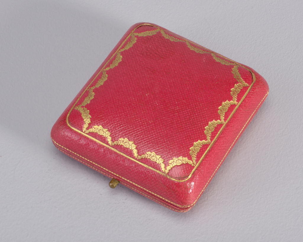 Rectangular in form with a plain gold surface with a sapphire in corner.  Has original red case with gold trim.