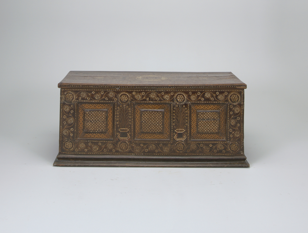 "Possibly Venetian; rectangular chest on base with overhanging lid, all with certosina decoration.  Three inset square panels on front, one on each end, with geometric inlay; inlaid stylized jardinière with flowers between front panels; arabesque flower and vine border around front and sides.  Hinged lid decorated with three large circles with stylized designs, filling ornament and linked ""S"" border.  Interior has shelf on two sides and deep compartment with hinged cover on third side. Inlay on interior."