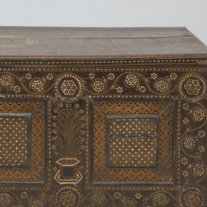 """Possibly Venetian; rectangular chest on base with overhanging lid, all with certosina decoration.  Three inset square panels on front, one on each end, with geometric inlay; inlaid stylized jardinière with flowers between front panels; arabesque flower and vine border around front and sides.  Hinged lid decorated with three large circles with stylized designs, filling ornament and linked """"S"""" border.  Interior has shelf on two sides and deep compartment with hinged cover on third side. Inlay on interior."""