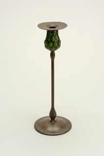 Tulip-shaped candle socket on tall slender stem with pine-cone shape above round plain base.  Socket pierced bronze with green glass blown inside.  Lip flares out, flat with ruffled edge.