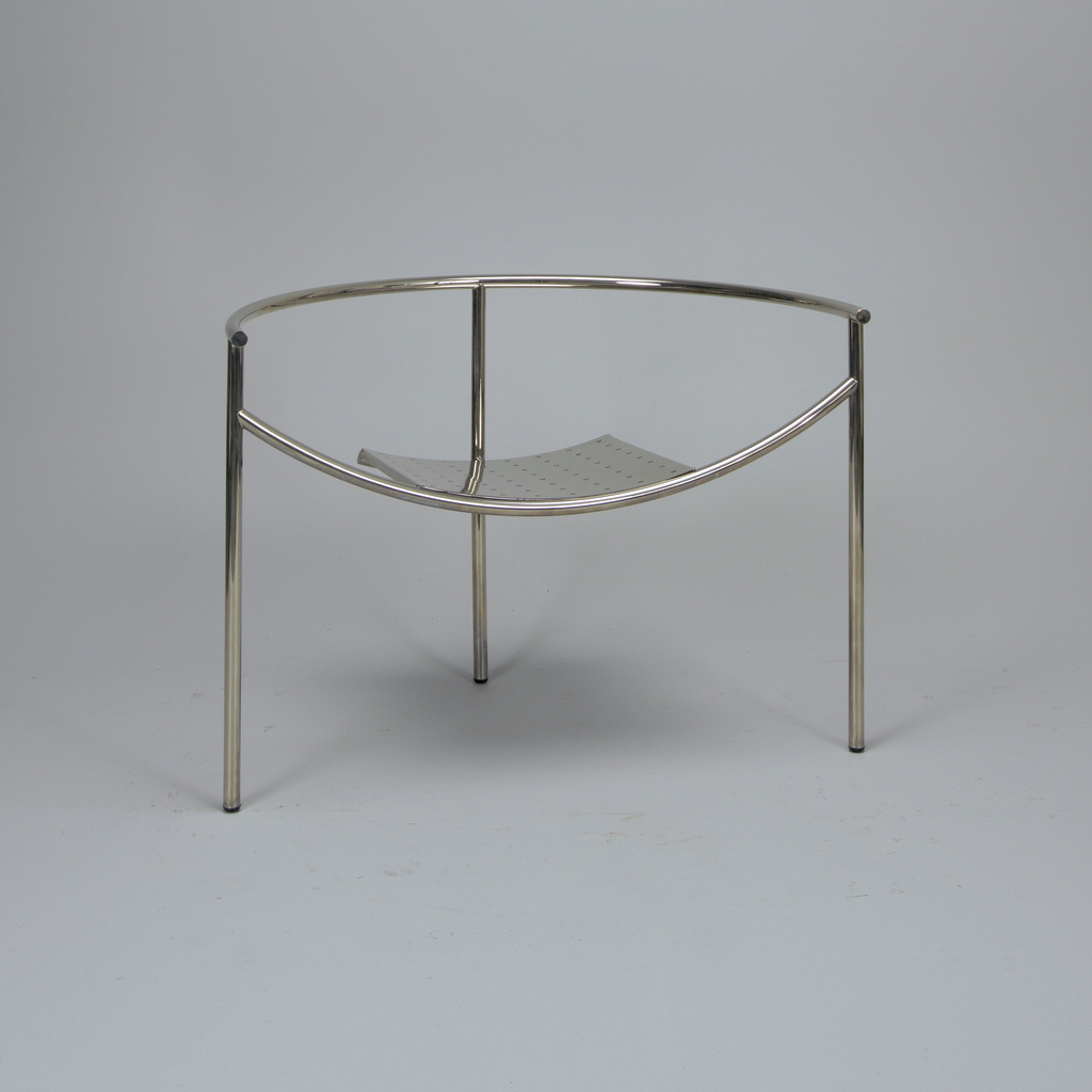 Upcurved square, perforated sheet metal seat mounted in frame of five arc-shaped tubular metal elements, one forming horizontal seat support, another the arms/back, and three as legs.