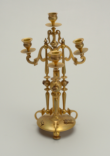 Three-legged gold decorative clock with three lower arms and one raised center arm for candlesticks. Insects are scattered among the candelabrum.