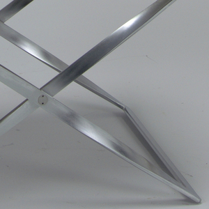X-shaped metallic folding base supporting a natural-colored canvas seat.