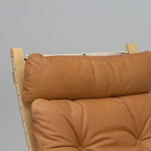 Curved wooden legs and back; honey brown colored leather upholstered cushion.