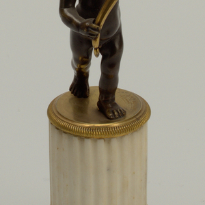 Each candlestick has a square plinth and cylindrical truncated fluted column of white marble with ribbed molding on base and top in gilt bronze. Striding bronze putto with one arm lifted and holding gilt bronze cornucopia with partly reeded candle socket with screwed baboche.