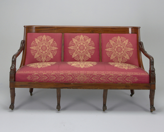 Sloping back divided into three sections, curved at ends; top rail scrolled.  Carved arms, with padded arm rests, in form of dolphin with curled tail joining back and head resting on corner blocks carved with lotus leaves.  Four fronts in form of lion legs with paw feet; two plain square back legs curved outward; casters added.  Upholstered in fabric of classical wreath and foliate pattern. (1926-22-352 a/f in Textiles Department)
