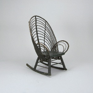 Carved seat; four cylindrical legs sit on rockers, stretchers between legs each side; tall curved back and arms formed from bent wooden branches, three vertical ribs on back, radiating up from seat.