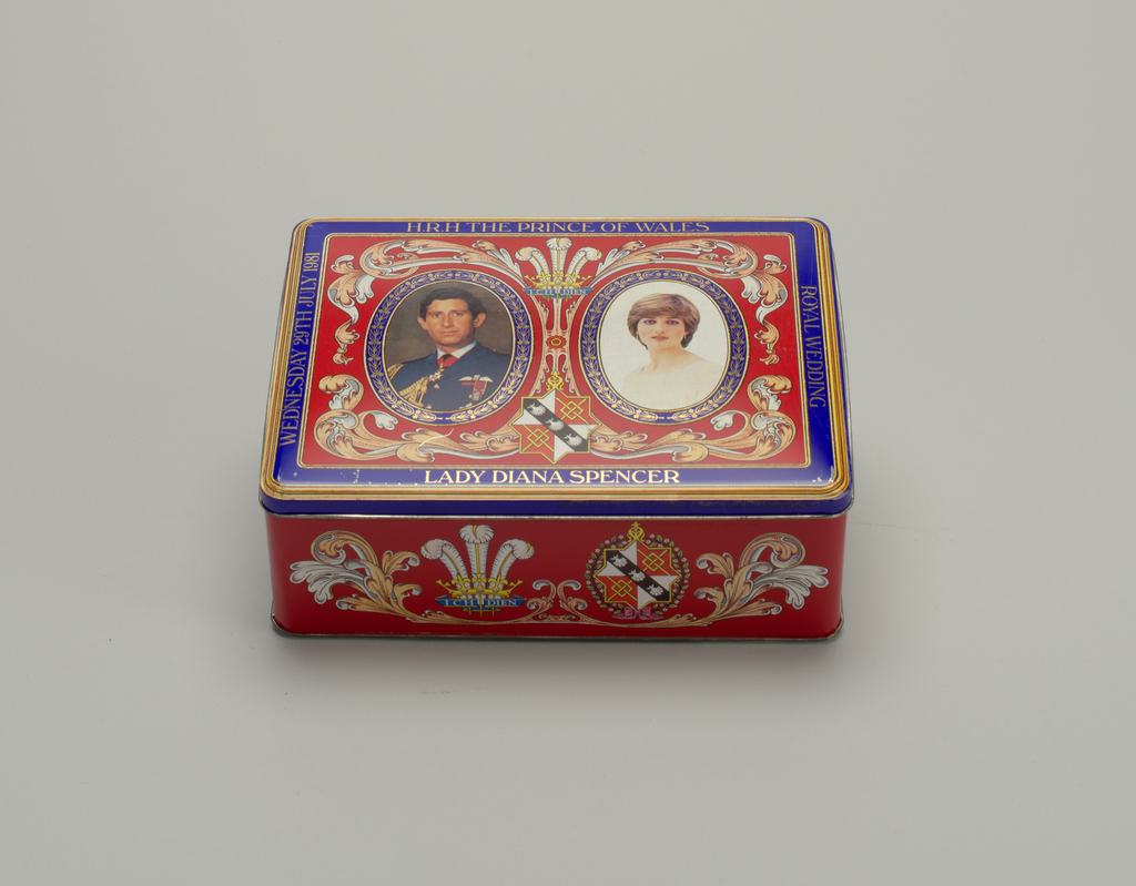 Red ground with blue and gold decoration showing family arms and mottos. On lid, portraits of the Prince of Wales and Lady Diana Spencer, enclosed in oval cartouches.  Inscribed: Royal wedding / Wednesday 29th July 1981