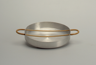 Round aluminum tray with semi-circular rattan-wrapped handles.
