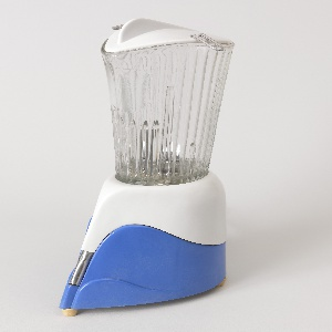 Wedge-shaped metal base in blue and white plastic housing (a); tall, ribbed glass container (b) sits on top; molded white plastic lid (c) with tab handle on top and bent metal wire tabs at sides.