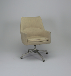 This high back swivel chair was designed to be the ideal seating unit for the executive.  The contoured back and arms provided superior comfort and mobility during long hours behind the desk.  The chair's four-pronged metal base was also available in wood.  This Jens Risom chair is upholstered in off-white, hand spun natural wool of Risom production.  The chair was also available upholstered in leather.