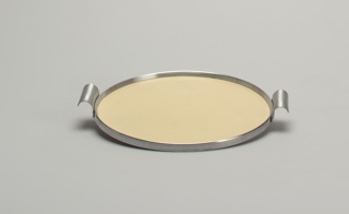 A circle chrome tray with a cream plastic inside. Tray also has two textured chrome handles on opposite sides.