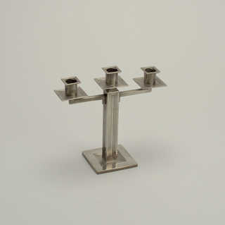 A candelabrum with a square base and a rectangle body. Smaller repeated rectangles and squares recede inward into the body and base. The candelabrum holds three candles in a row. This candelabrum is part of a pair.