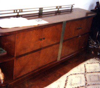 Long, veneered rectangular form with rounded front corners; brass rail attached to top rear;  central section with four hinged doors, each with brass knob; drawers inside; narrow vertical strip of plain brass attached at center; open shelves at sides. Base with four square reeded feet.
