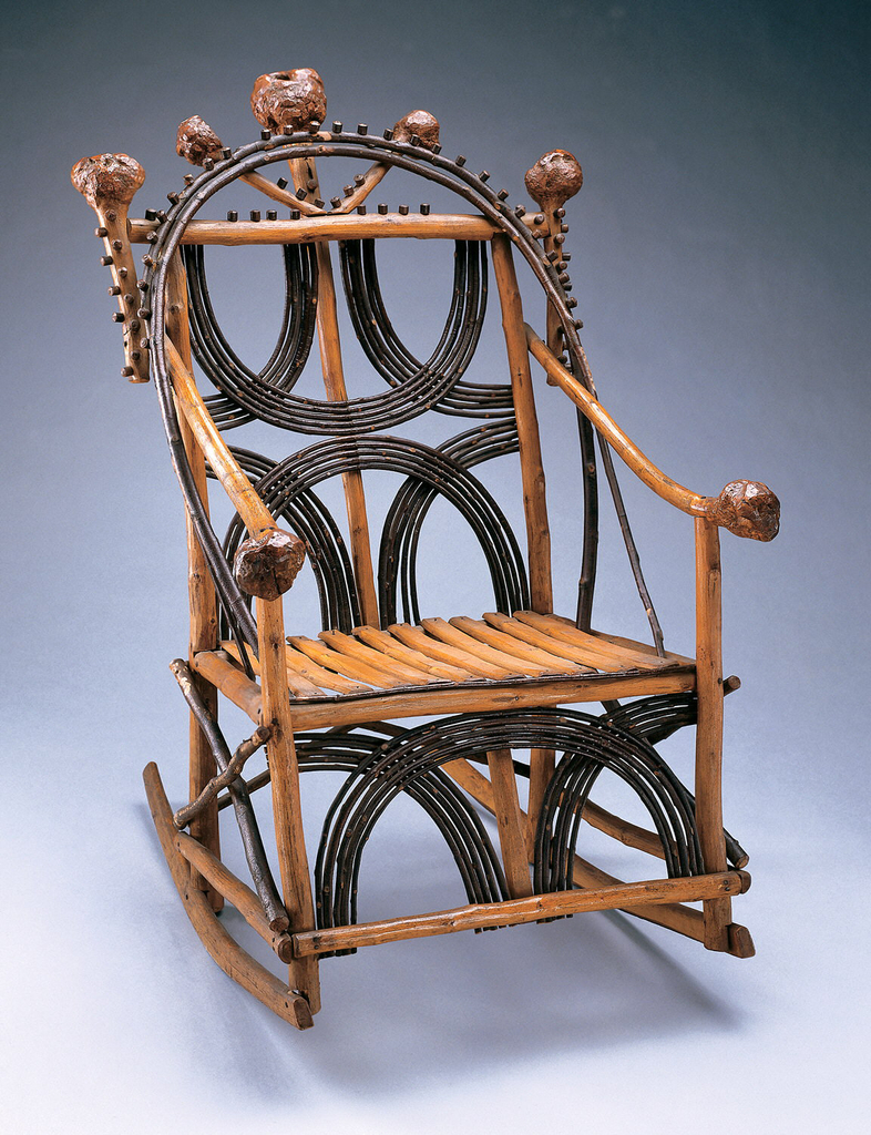 This rocking chair has a frame of light wood with large bulbous ends. Along the top of the chair are five of the large bulbous ends creating a high back. The rest of the chair consists of darker semi-circles weaved into the frame and each other.