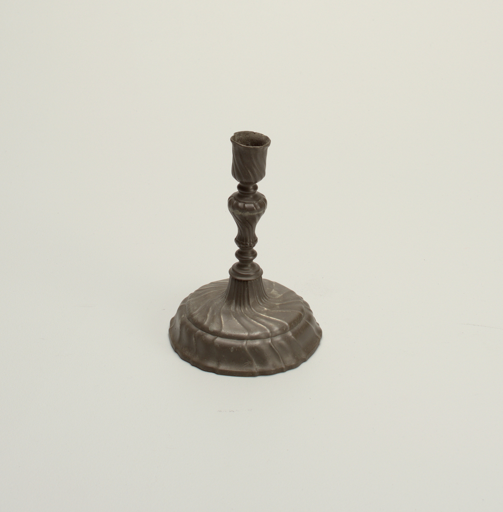 Gadrooned spreading foot, baluster stem and rimless candle socket.
