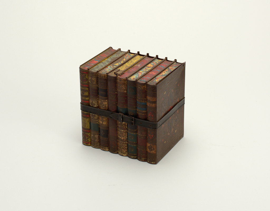 """Biscuit tin in the form of eight bound books, with hinged lid as marbled pages and edges of book covers; pull tab as bookmark.  The sides finished to appear as polychromed tooled leather, the front as book spines with the following titles: """"History of England,"""" Pilgrims Progress,"""" """"Burns,"""" Pickwick Papers,"""" """"Robinson Crusoe,"""" """" Gullivers Travels,"""" """"Self Help,"""" and """"Shakespeare;"""" all bound with simulated leather strap and buckle."""