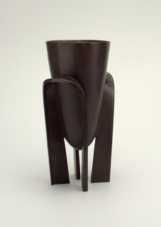 Tall, flaring vase with rounded bottom; four legs formed from two long arched straps attached to body at opposite sides.