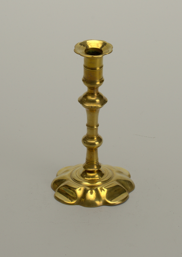 Molded baluster stem, on quatri-lobate stepped petal bases, the scalloped drip pans on the campana-shaped girdled candleholder above a scalloped knop; stick unscrews in two places to form three sections.