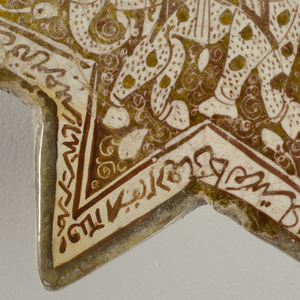 Shaped as a six-pointed star; painted in brown and white with luster glaze:  elephant with large and small dots in center with floral motifs, surrounded by white border with brown calligraphy.