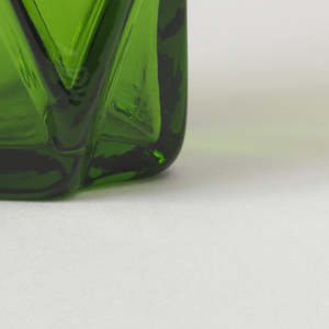 Irregularly shaped transparent green body, the uneven surface appearing as a series of broken up planes and angles.