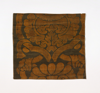 Length of batik-printed velvet with a large-scale baroque pattern of  leaves and strapwork in a symmetrical arrangement in light brown on a dark brown ground. The depth of color is achieved by block printing dense cotton velvet with hot wax, cracking the waxed cloth, dyeing, removing the wax, and dyeing again.