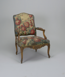 Louis XV armchair with back, seat and top of arms upholstered in red-to-blue Aubusson tapestry with floral design; domed metal tacks along edges of fabric; carved scrolling and floral decoration at center front of seat rail, knees, feet, and arms.