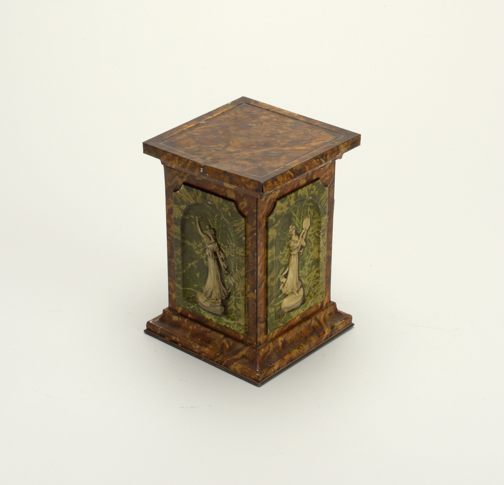 Tin resembling a brown marble pedastal inset with green marble niches and classical female figures. Flat top.