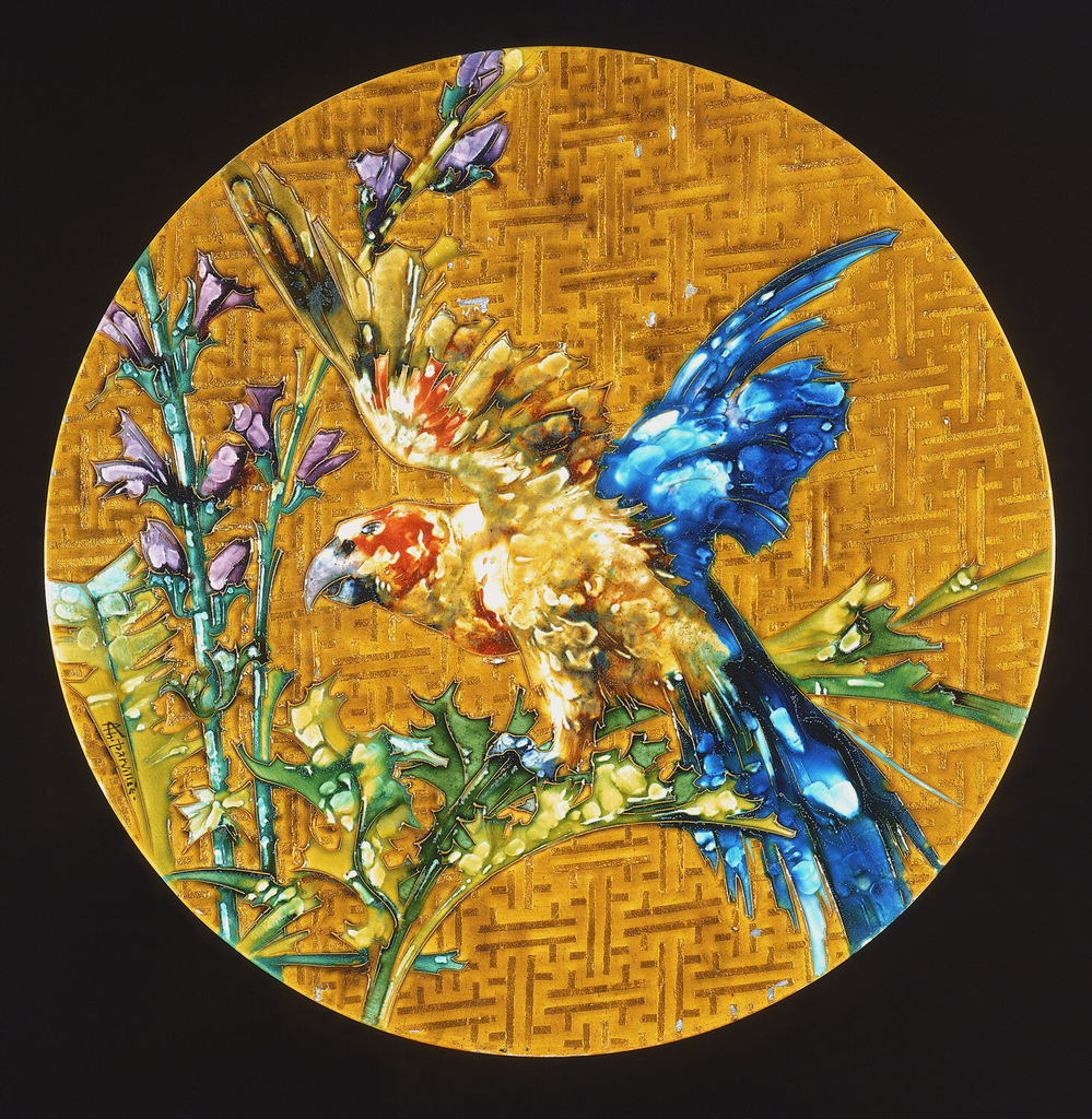 Circular plate with gold colored crosshatched ground deecorated with scene of colorful bird (parrot?) with outstretched wings on tall stalks of purple and yellow followering plants.