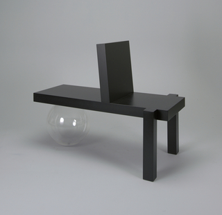 Black rectangular bench seat bisected by square back rest; two legs, square in section, at one end, plexi-glas sphere as support at the other.