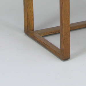 Dark brown wood frame comprising rectangular back, seat, arms and base; seven vertical tan leather straps on back, ten interlaced straps on seat.