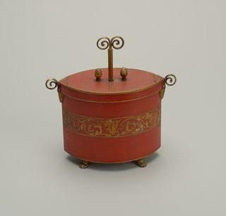 Painted oval in plan, with four paw feet, two volute handles and two acorn knobs on flat, two-leaved hinged cover. Red ground with band of gilt foliate scrolls.