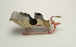 Two-seated ivory colored sleigh with blue and gold trim, black and blue upholstery. Chassis of scrolled wires, runners, and small wheels, in red with yellow stripe. At front, an ornamented swan's head of gilded lead.