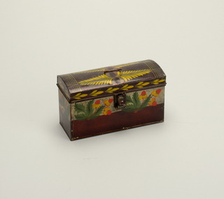 Rectangular box with hinged cover domed from front to back. Ring bail handle on cover, and hinged harp fastening. Painted black with horizontal band of dull gray and upper half of body on front and two ends only. On the front of band and extending below are sprays of acorns and leaves; on each end a small branch of cherries. Colors are vermillion red, yellow, and green, with black lines. Cover has two double sprays of yellow fond-type leaves, with some red, and yellow lines across ends. A continuous border of repeated 3-leaf motif in yellow extends across ends and front.