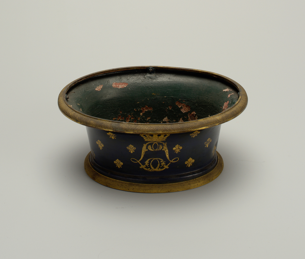 Oval, with straight sides and everted lip. Outside painted dark teal, with gilt interlacing double L, crowned, and scattered fleur-de-lis. Inside painted green. Foot and rim mounted in ribbed brass.
