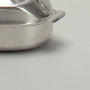 Aluminum pan and cover. Pan in oval shape with everted handles that curve downward. Cover has concentric, stepped shape with handle on one side where the cover is flattened.