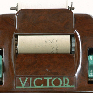 Brown metal rectangular housing with turquoise and black plastic buttons and crank on right side.