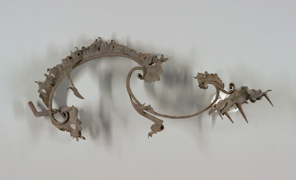 Made of strap-like scrolls of iron joined in reverse position and terminating in a leaf-shaped bobeche with four prickets, the central one threaded at the base.  Outer edges of scrolls with double frill of continuous, pierced leaf ornament.